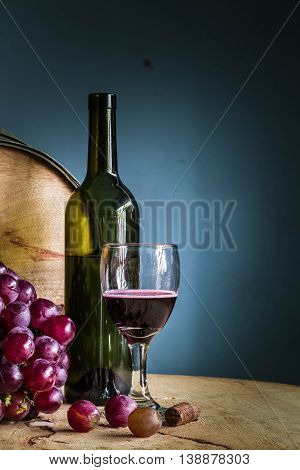 Red wine grapes on a wooden table in winery.