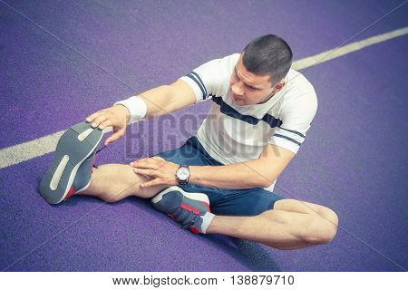 Man stretching hamstring leg muscle on the purple running track while preparing for morning workout. Caucasian sport fitness model outdoors. Recreation and healthy lifestyle concepts.