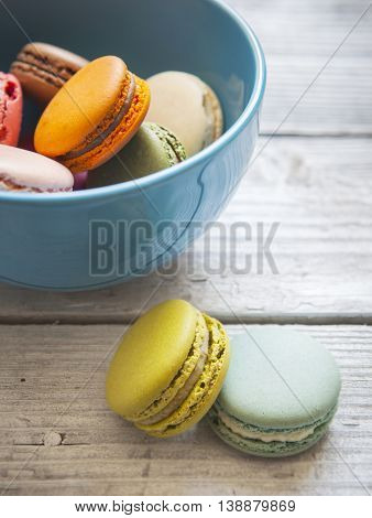 Colorful macaroons in blue bowl and on the wooden table. Testy breakfast