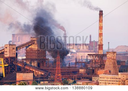 Industrial landscape in Ukraine. Steel factory with smog at sunset. Pipes with smoke. Metallurgical plant. steelworks iron works. Heavy industry. Ecology problems atmospheric pollutants.