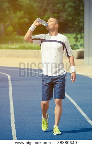 Portrait of thirsty sportsman drinking water from the plastic bottle and walking on the blue running track. Trees and other greenery in the background. Ideal for bottle pack shoot adding.  Sport, fitness, jogging, nature and healthy lifestyle concepts.