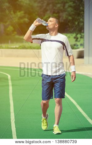Portrait of thirsty sportsman drinking water from the plastic bottle and walking on the green running track. Trees and other greenery in the background. Ideal for bottle pack shoot adding.  Sport, fitness, jogging, nature and healthy lifestyle concepts.