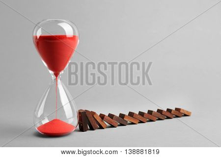 Dominoes and hour glass on grey background