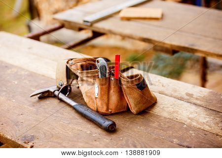 Carpenters bag with belt full of tools laid on wooden table. Construction site.