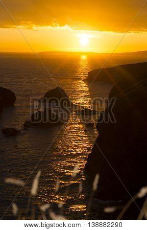 beautiful sunset over the coastal rocks with wild highl grass on the wild atlantic way