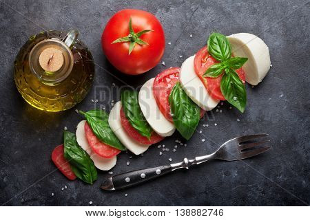 Caprese salad. Mozzarella cheese, tomatoes and basil herb leaves on cutting board over stone table. Top view
