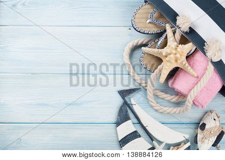 Beach accessories. Bag, towel and flip-flops on wooden background. Top view with copy space