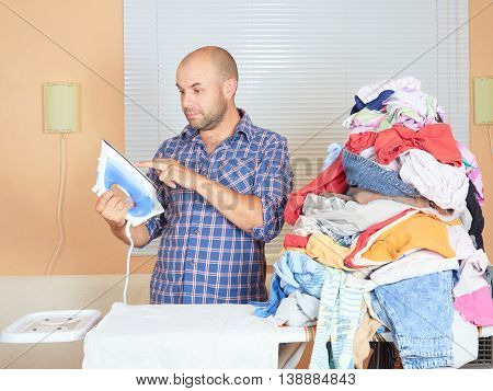 Caucasian Man Touches A Finger Iron To Ironing Clothes.