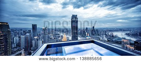 cityscape and skyline of chongqing in cloud sky at twilight on view from empty patio on modern buildings