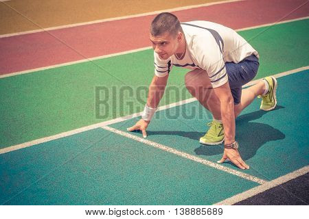Young athlete at the starting line on blue running track. Running tracks in different colors. Sport, fitness, healthy lifestyle concepts.