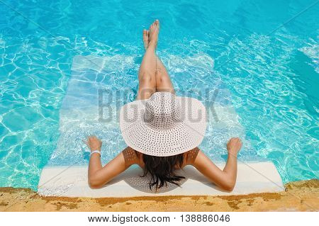 woman in a big hat lying on a lounger by the pool.