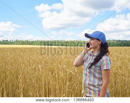 Young Pretty Farmer Girl Standing In Yellow Wheat Field And Talking On The Phone.
