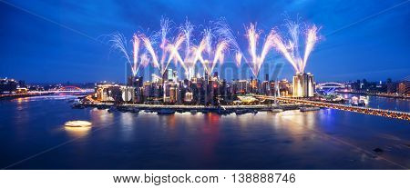 cityscape and skyline of downtown with colorful fireworks near water of chongqing at twilight