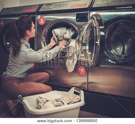 Beautiful woman doing laundry at laundromat shop.
