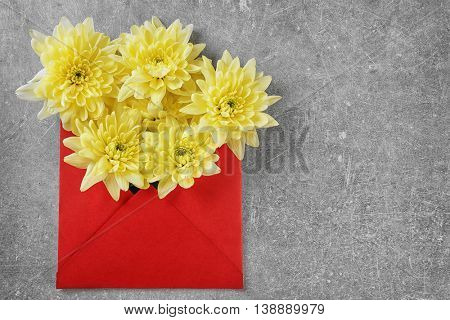 Yellow chrysanthemum in red envelope on table