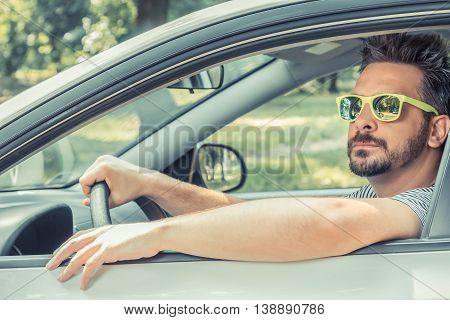 Portrait of young driver wearing sunglasses in driver's seat. Vacation and travel concepts.