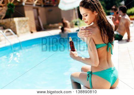 Beautiful woman applying skin uv protection lotion
