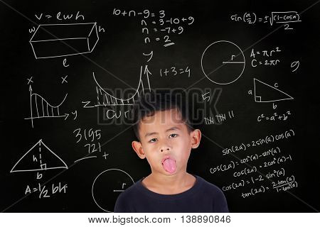 Portrait of little Asian student boy with his tongue out getting sick and bored of math lesson over blackboard with mathematics schemes doodle drawn on it