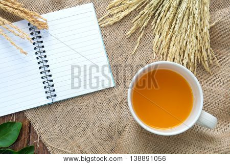 Orange juice and sweetmeat with notebook and pen on Sackcloth brown.Top view focus.
