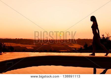 Beautiful woman enjoying summer sunet by her pool