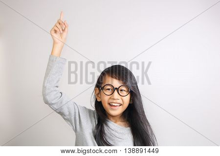 Portrait of beautiful little Asian student girl smiling enthusiastic and raise her hand and pointing finger up to get attention from teacher in class