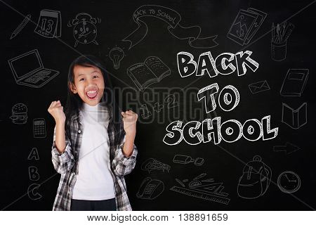 Education concept portrait of happy cute beautiful Asian girl showing enthusiastic winning gesture shout with joy of victory over blackboard with Back to School written on it