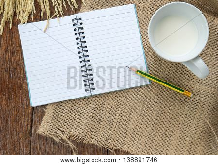 Milk and sweetmeat with notebook and pen on Sackcloth brown.Top view focus.