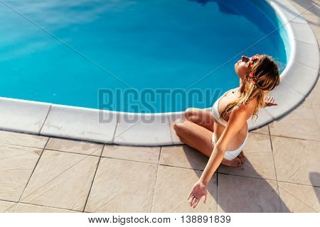 Beautiful sexy blond woman meditating at pool