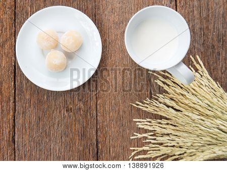 Milk and sweetmeat with rice drying on wooden floor.Top view focus.