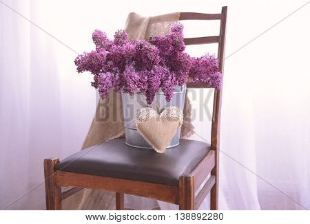 Lilac bouquet in metal bucket on leather chair