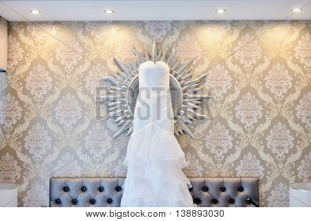 Beautiful White Wedding Dress For Bride Indoors On The Bed. Beauty Of Bridal Gown For Marriage. Fema