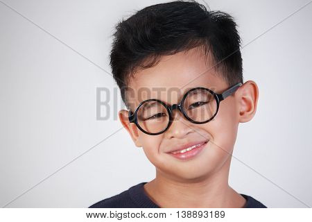 Portrait of little Asian boy wearing glasses smiling happily