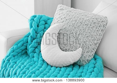 Stylish pillows with turquoise plaid on white couch