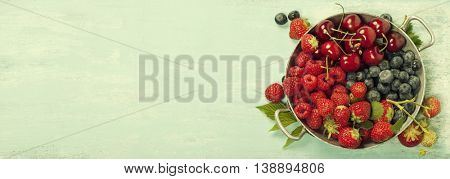 Mix of fresh berries  on blue wooden background - Summer Organic Berry over Wood. Agriculture, Gardening, Harvest Concept