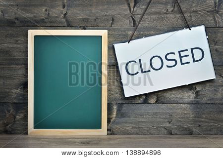 School board and closed message on wooden table