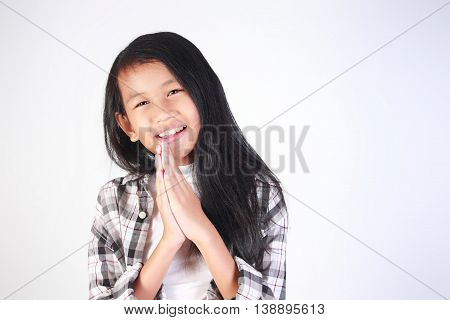 Portrait of little Asian girl begging for forgiveness gesture