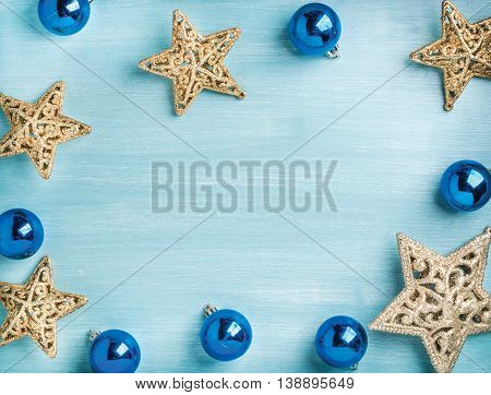 New Year or Christmas background: golden stars and blue glass balls over blue painted wooden backdrop, top view, copy space