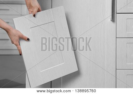 Female hands holding sample of wooden panels for furniture and door