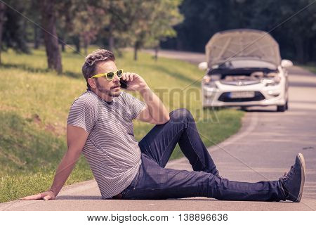 Young modern man sitting on the asphalt and making call with road assistance service. Car with raised hood at the roadside.