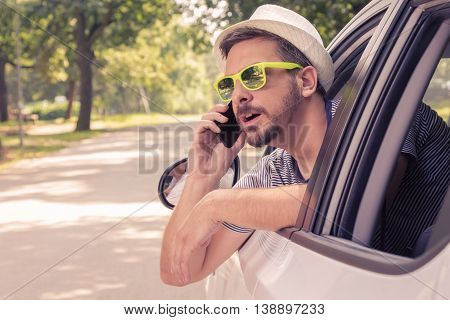 Portrait of young driver with hat and sunglasses talking on smartphone from the car. Vacation and travel concepts.