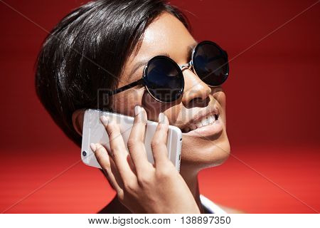 Close up portrait of beautiful smiling young woman with short hair wearing round hipster sunglasses having phone conversation on mobile phone with happy look sharing latest news with her best friend