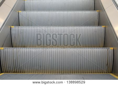 Zooming image of escalator steps while escalators are moving up