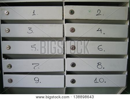 Grey mailboxes with numbers and key pattern