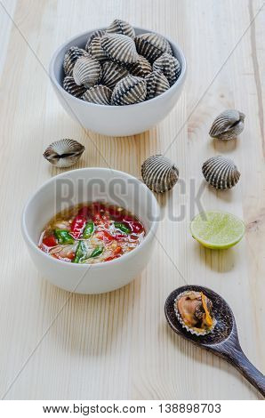 Steamed Blanched Clams In White Bowl And Spicy Dipping Sauce On Wooden Background