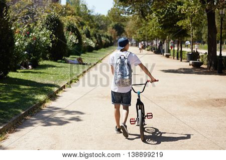 Healthy Lifestyle Concept. Back View Of Teenage Boy In Street Wear, Carrying Backpack And Walking Wi