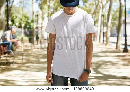 Portrait Of Teenage 15-year Old Boy Wearing Cap Over His Eyes, Pulling Down His White Blank T-shirt