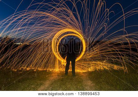 Person standing in front of a steel wool circle looking like a portal trough time