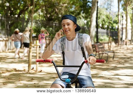 Leisure And Vacations. 15-year Old Schoolboy In Stylish Street Wear Talking On The Phone While Sitti