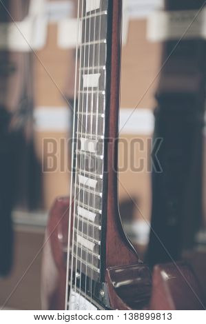 Electric guitar fingerboard against colorful background .