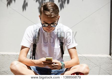 Handsome Caucasian 15-year Old Boy Wearing Backpack Sitting On The Pavement Using Electronic Gadget.